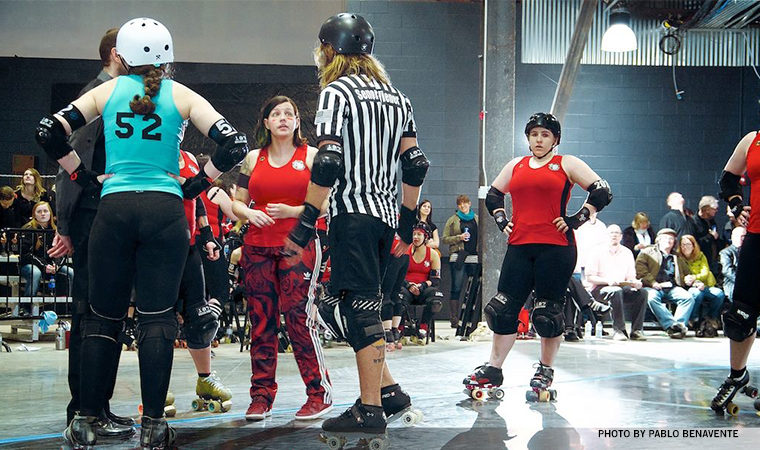 Roller derby game - the coach from the red team is talking with the referee